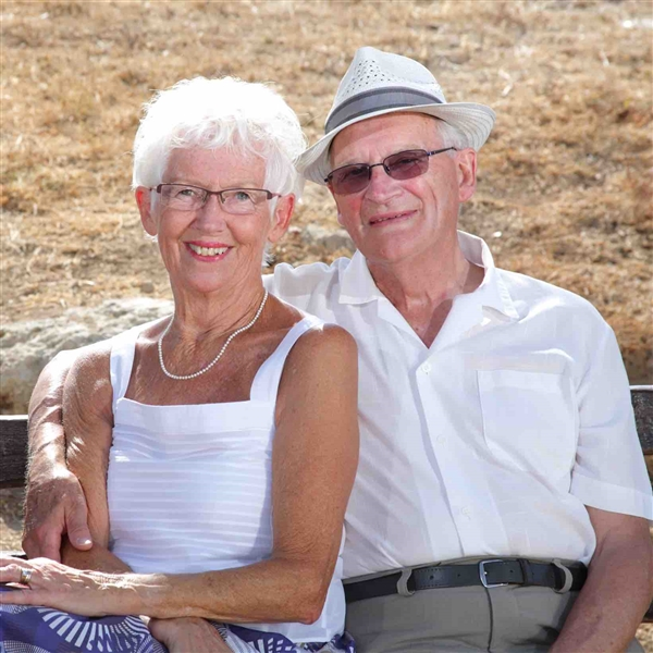 Older couple sitting on a bench smiling